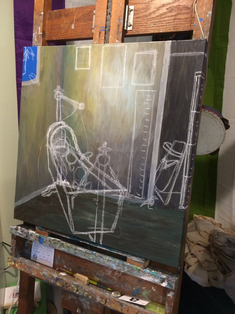An unfinished painting on an easel. The walls of the room depicted in the painting have been painted as has some of the floor. There is a window slightly visible in the upper left corner. On the right side of the image a dark space has been painted indicating a closet. White chalk has been used to sketch a bassinet in the corner of the room and an empty cradle board tucked away in the closet. Four squares have been sketched on the wall behind the cradle indicating positioning for paintings and a growth chart. Birds have been sketched entering the room through the open window.