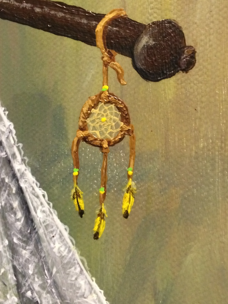 A close up detail of a painting shows a small dream catcher hung with yellow canary feathers. The texture of the canvas and brush strokes are visible.