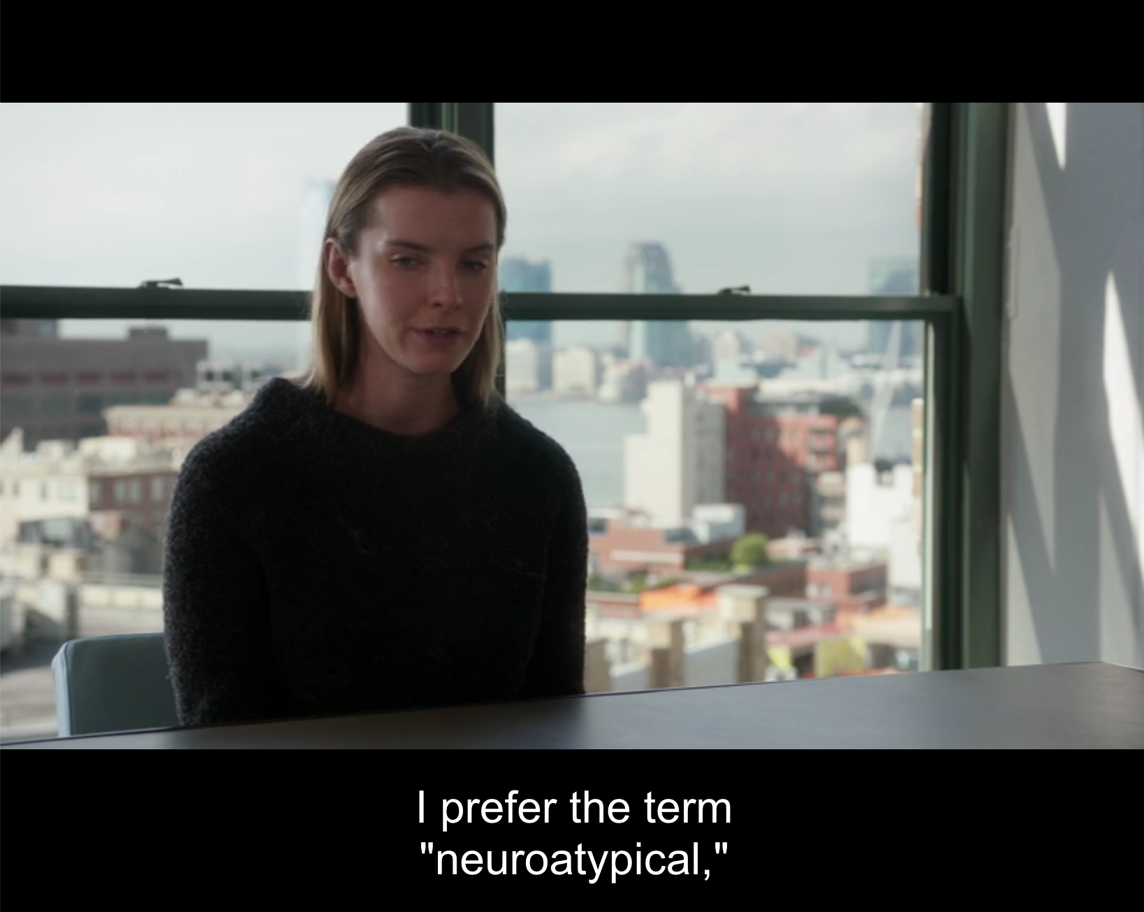 "Fiona sits rigidly at a conference table with her hands folded in her lap. A view of New York is visible through the window behind her. A subtitle reads: ""I prefer the term ""neuro-a-typical"" (Elementary. 2016a)."
